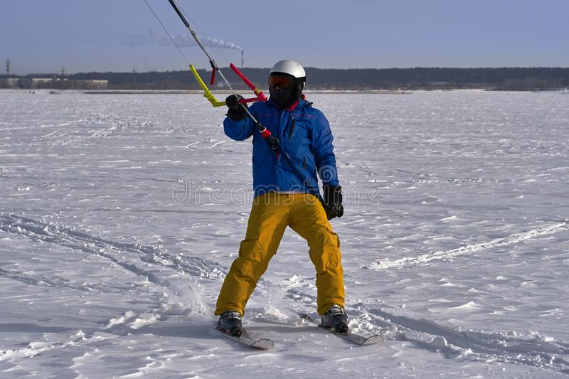 Un atleta de sexo masculino enganchó a la nieve kiting en el hielo de un lago nevoso grande Él va a esquiar en la nieve Día escar foto de archivo libre de regalías