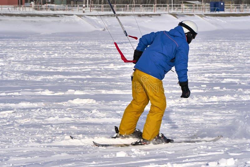 Un atleta de sexo masculino enganchó a la nieve kiting en el hielo de un lago nevoso grande Él va a esquiar en la nieve Día escar imágenes de archivo libres de regalías