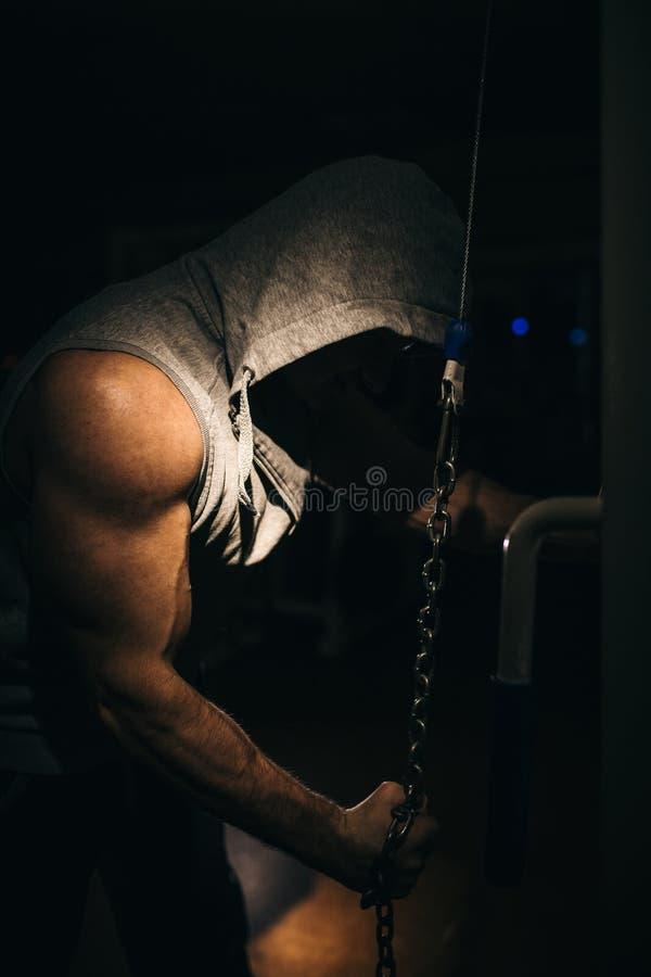 Un atleta fuerte hace ejercicios del tríceps con una cadena en un simulador de los deportes fotos de archivo