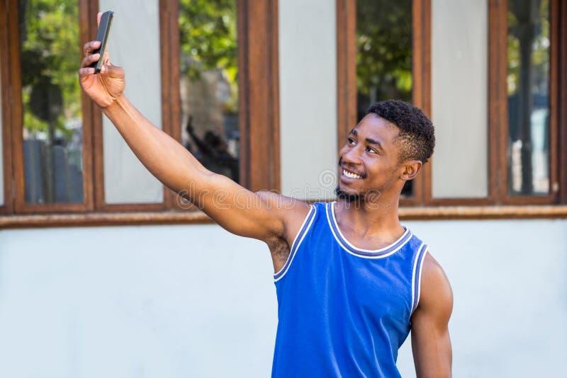 Un atleta hermoso feliz que toma un selfie imagen de archivo