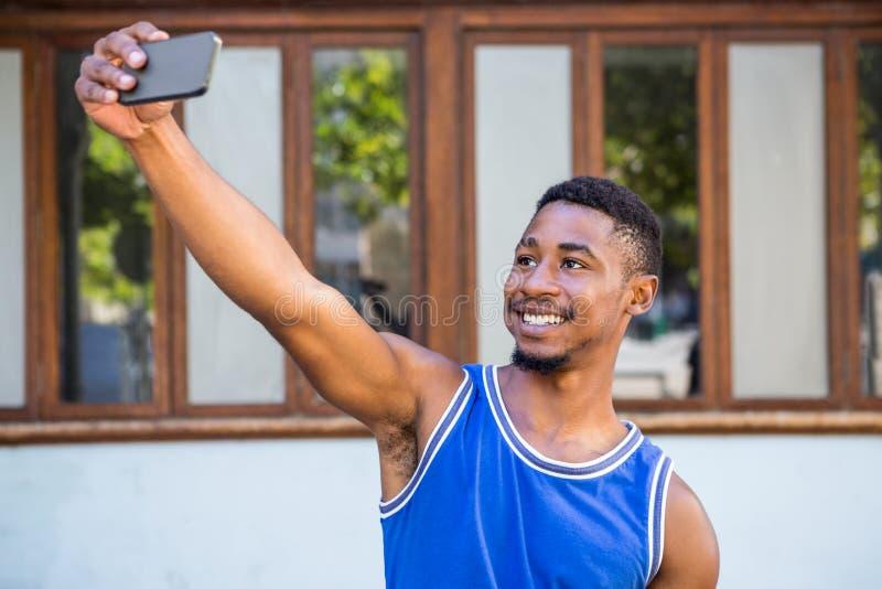Un atleta hermoso feliz que toma un selfie fotos de archivo libres de regalías