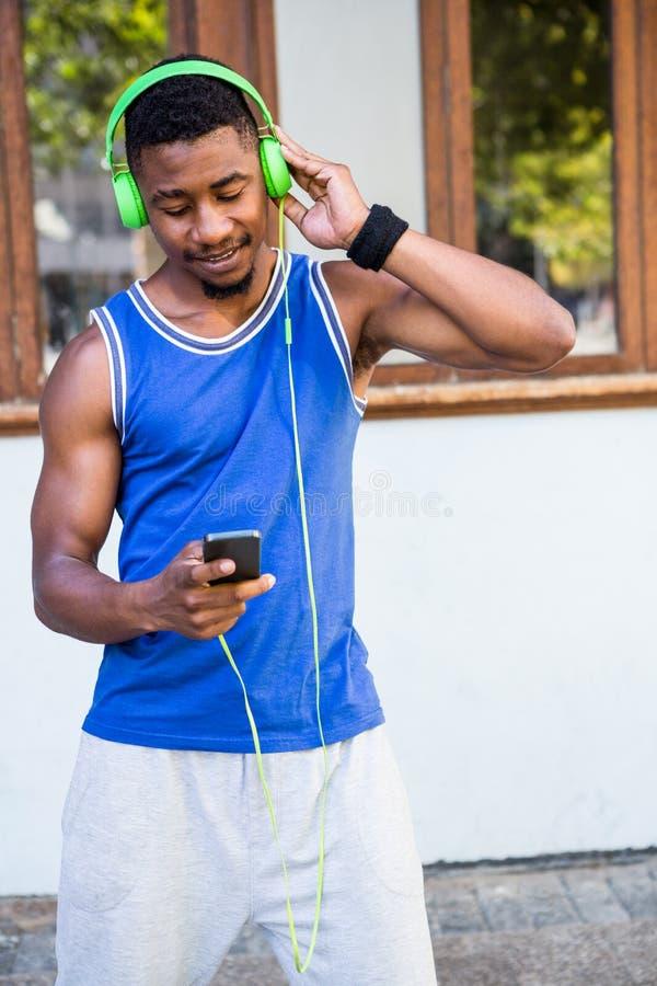 Un atleta hermoso que escucha la música fotografía de archivo libre de regalías