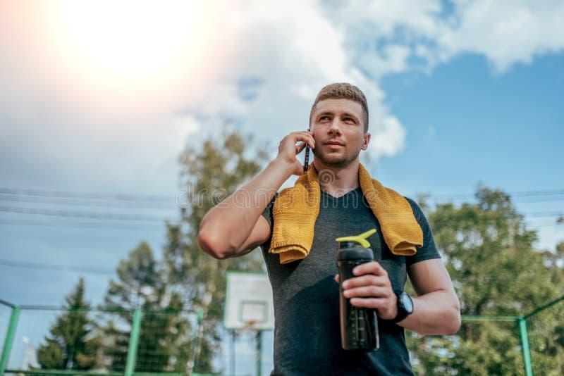 Un atleta maschio, la città dopo un allenamento, chiamate dell'estate sul telefono, tiene in sua mano un agitatore, una bottiglia immagini stock libere da diritti