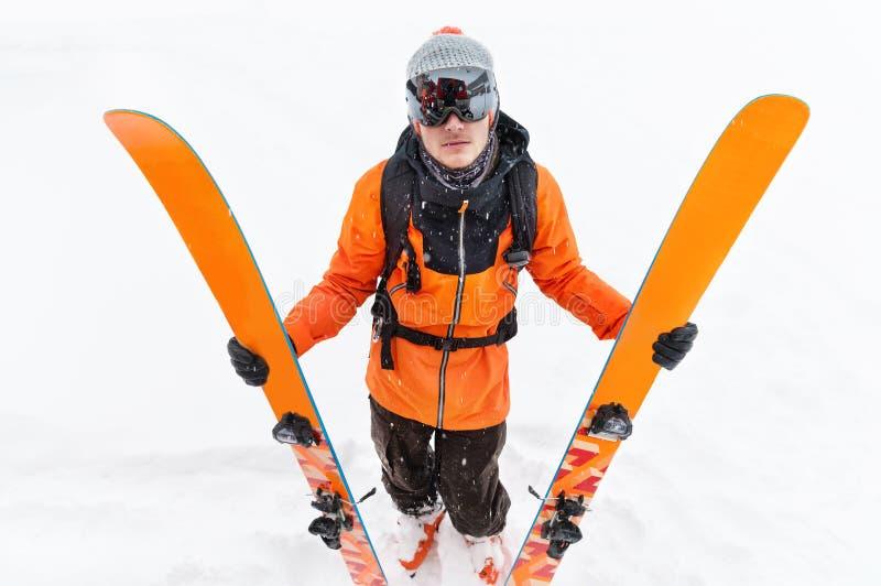 Un atleta professionista dello sciatore in un vestito nero arancio con una passamontagna nera con gli sci nei suoi supporti delle immagini stock