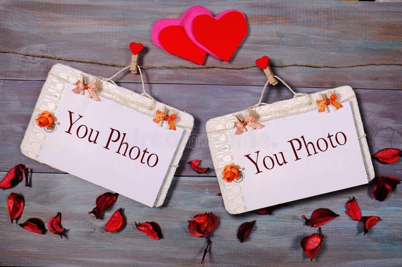 Un'attaccatura di carta di due foto da rope con le mollette per il bucato su fondo di legno fotografia stock libera da diritti
