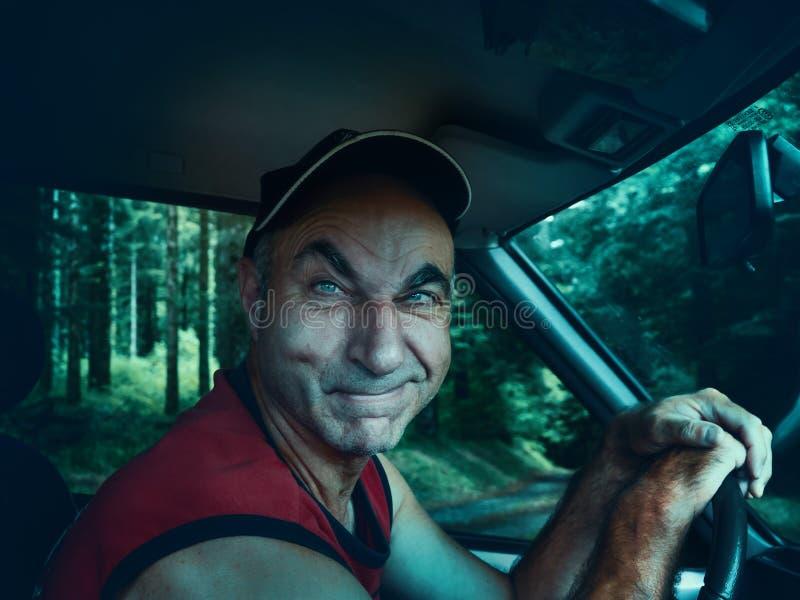 Un autista sospettoso dietro la ruota invita il passeggero alla sua automobile fotografie stock libere da diritti