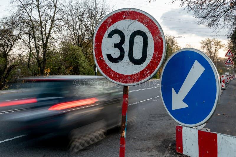 Un'auto ad alta velocità blu con effetto sfuocato in prossimità del semaforo che limita la velocità massima a 30 km/h fotografia stock libera da diritti