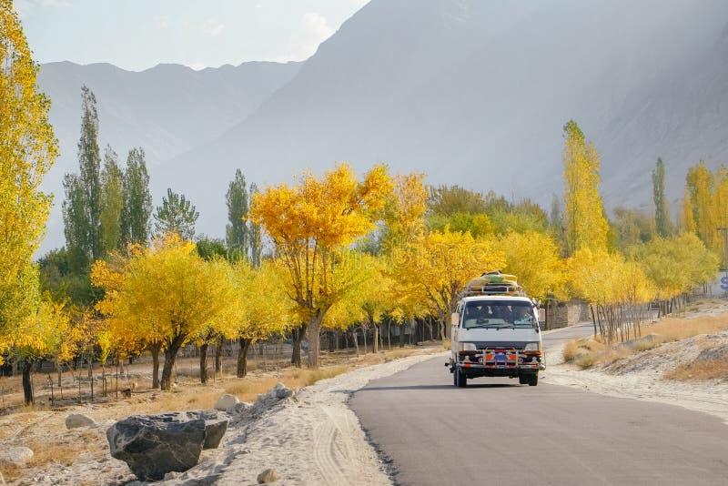 Un autobús urbano con los bolsos del equipaje en el tejado que corre a lo largo de árboles en otoño contra cordillera fotos de archivo libres de regalías
