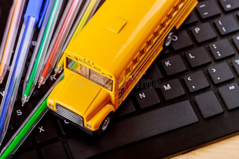 Un autobus scolaire jaune de jouet sur les crayons et l'ordinateur colorés de clavier images libres de droits