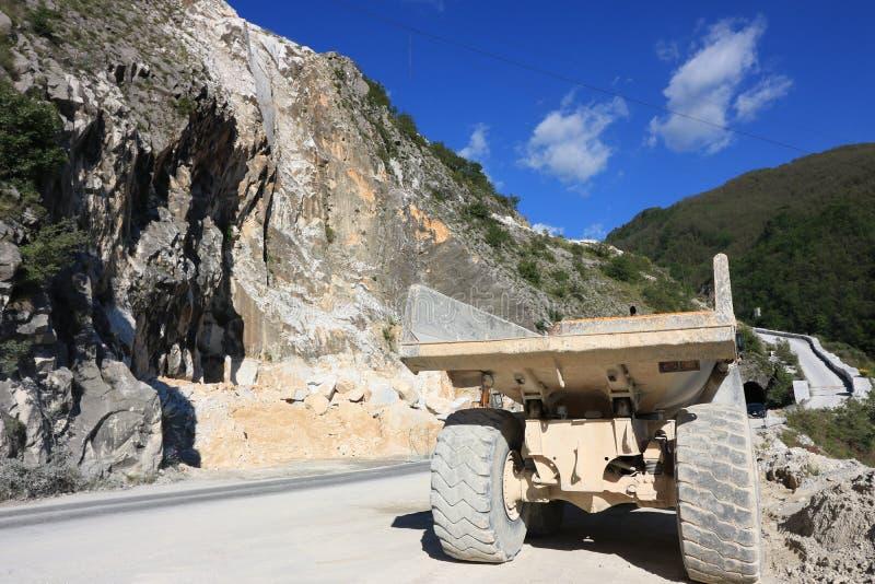 Un autocarro con cassone ribaltabile utilizzato in una cava del marmo di Carrara Grande dum giallo immagine stock libera da diritti