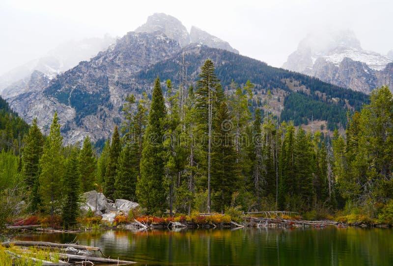 Un automne tôt de neige sur le lac photos stock