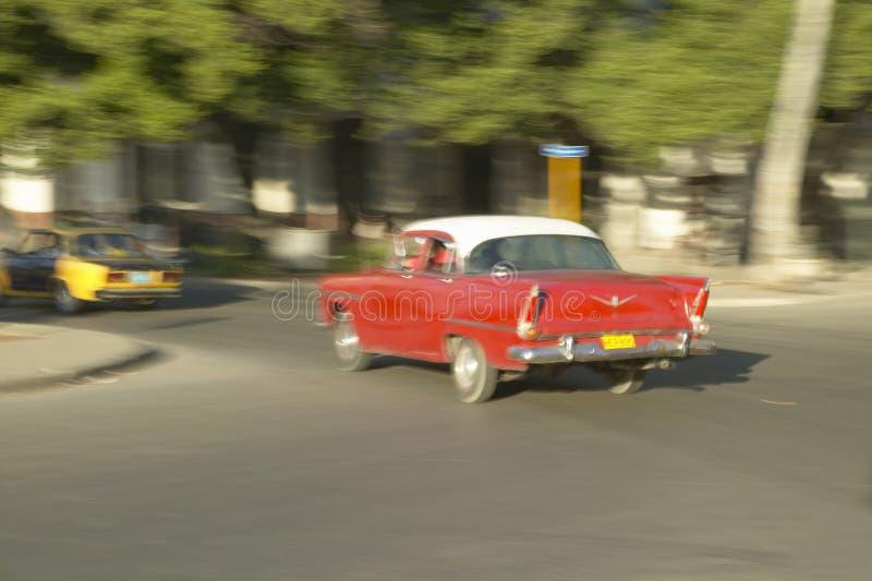 Un'automobile americana degli anni 50 che accelera tramite le vie con luce solare su a Avana, Cuba immagine stock