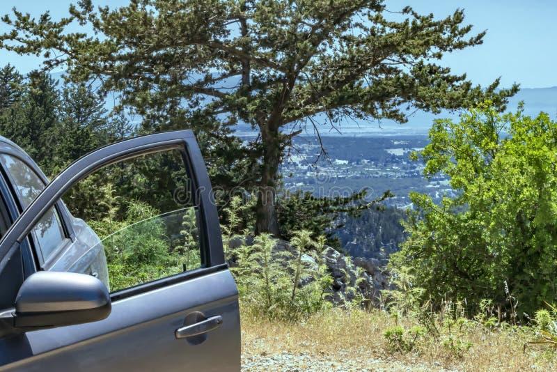 Un'automobile con una porta aperta sta su una collina o su una cima di una montagna con la vista sulla valle Priorit? bassa di pa fotografia stock