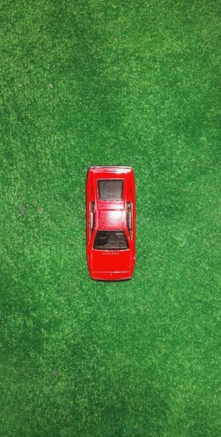 Un'automobile rossa di modello in un tappeto verde immagini stock libere da diritti