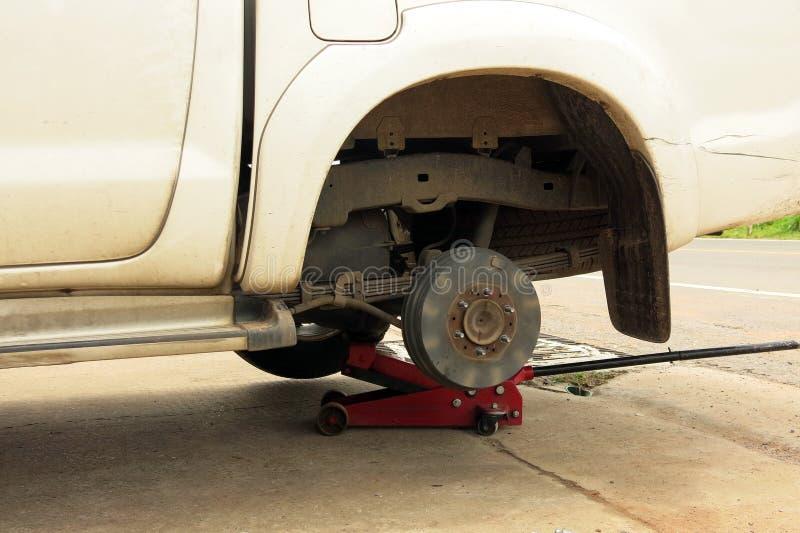 Un'automobile sporca bianca senza un pneumatico nella riparazione del processo fotografia stock libera da diritti