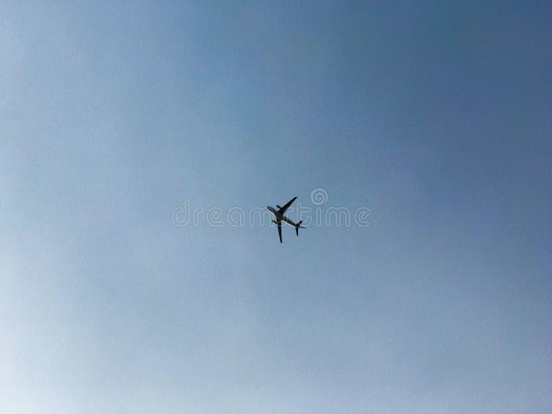 Un avión de pasajero grande con las moscas de las alas, se eleva arriba en el cielo azul foto de archivo