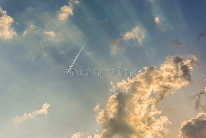 Un avión de pasajeros de altos vuelos y rayos de sol en un cielo azul foto de archivo libre de regalías