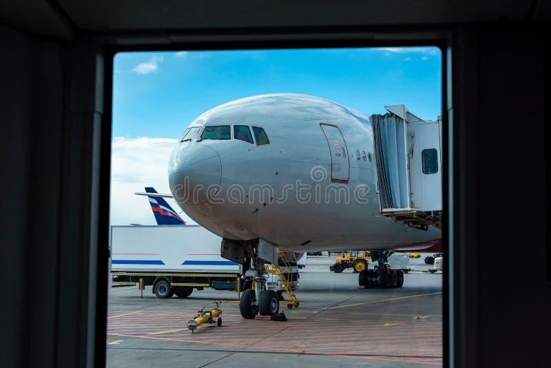 Un avión de pasajeros se está colocando en el aeropuerto en un espacio que parquea que aguarda salida, el proceso de la preparaci foto de archivo libre de regalías