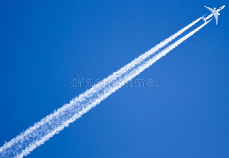 Un avión del vuelo deja una raya en el cielo fotografía de archivo libre de regalías