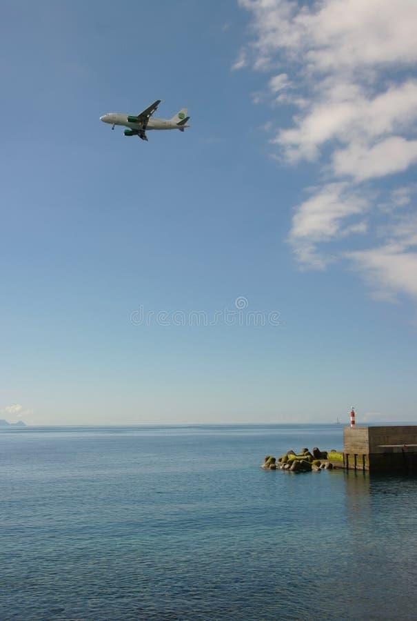 Un avion de vol dans le ciel au-dessus de l'océan images libres de droits