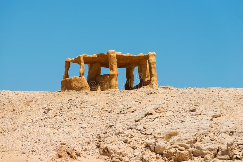 Un axe en pierre jaune debout isolé, seul se tenant dans le désert sur une colline photos stock