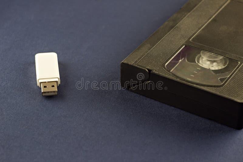 Un azionamento istantaneo bianco su un fondo blu e su una videocassetta, informazioni immagini stock libere da diritti