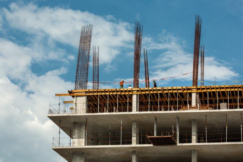 Un bâtiment à plusiers étages en construction avec quelques petits travailleurs construisant contre le ciel Les nouvelles maisons photo stock