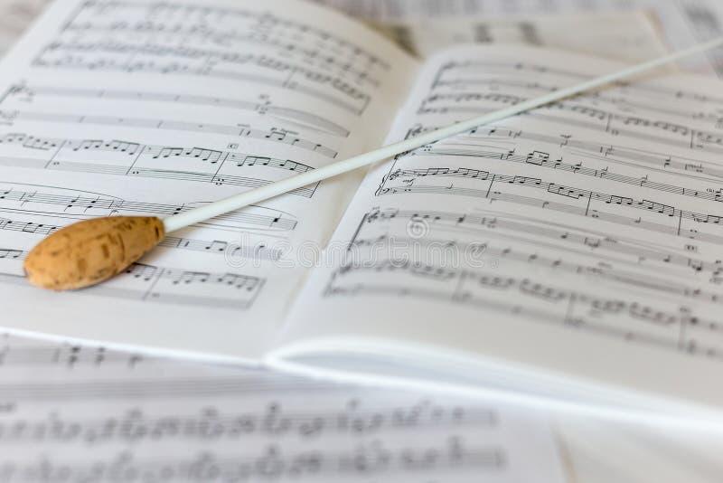 Un bâton naturel de conducteurs sur le score orchestral image libre de droits