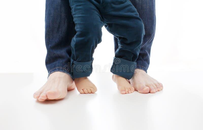 Un bébé apprend la marche avec le père ensemble sur le blanc, leurs pieds sont nu photos stock