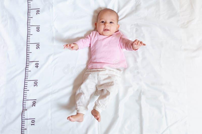 Un bébé heureux de quatre mois dans des vêtements blancs roses se trouvant sur un lit sur lequel une règle de mesure pour la croi images stock