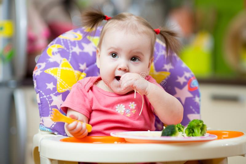 Un bébé an mignon dans le highchair avec des pâtes dans la cuisine à la maison image libre de droits