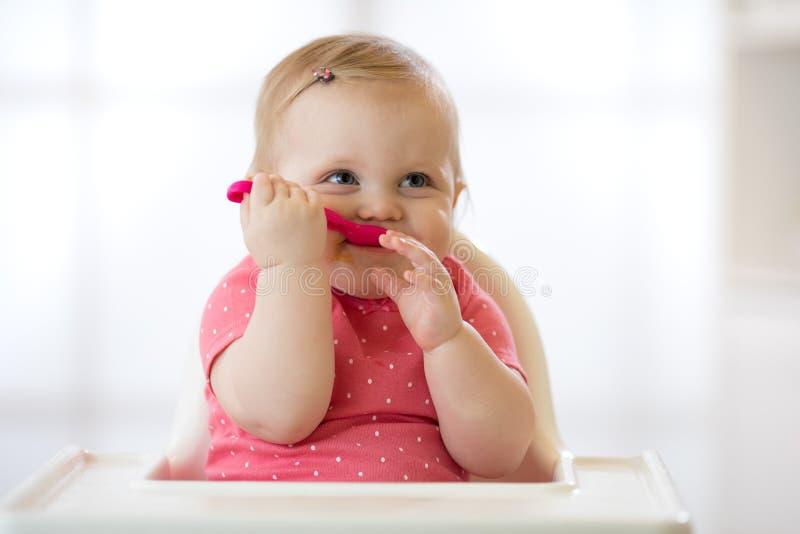 Un bébé an mignon dans le highchair avec la cuillère dans la cuisine à la maison photographie stock