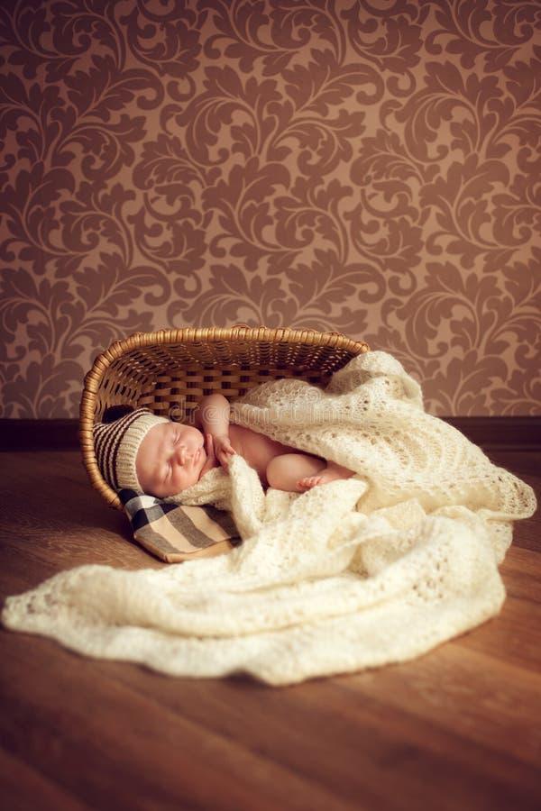 Un bébé nouveau-né dort dans une salle confortable dans un panier, couvert d'a photographie stock