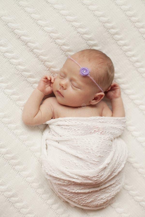 Un bébé nouveau-né dort sur un plaid blanc image libre de droits
