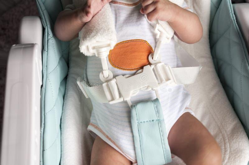 Un bébé nouveau-né est attaché dans un highchair pour alimenter avec un harnais de cinq points Foyer sélectif image stock