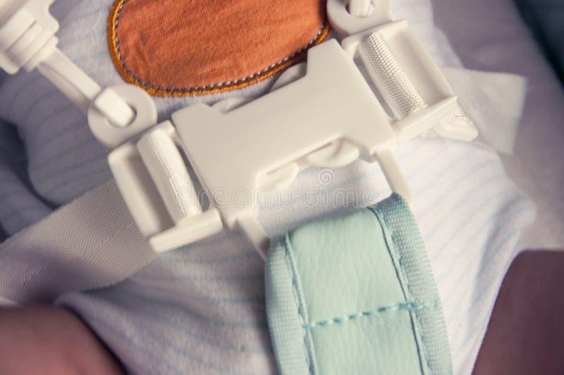 Un bébé nouveau-né est attaché dans un highchair pour alimenter avec un harnais de cinq points Foyer sélectif photographie stock