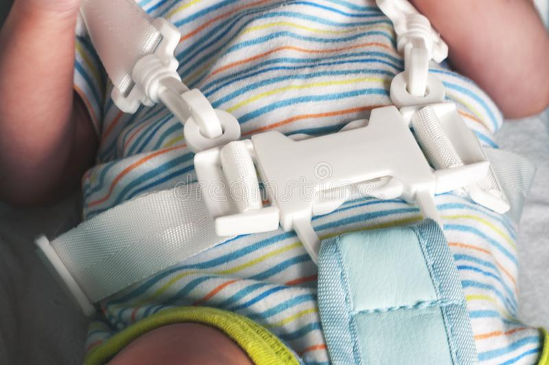 Un bébé nouveau-né est attaché dans un highchair pour alimenter avec un harnais de cinq points Foyer sélectif photo stock