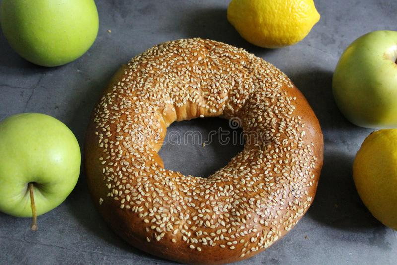 Un bagel frais avec les graines de s?same Sont tout pr?s les fruits - des pommes et des citrons image libre de droits