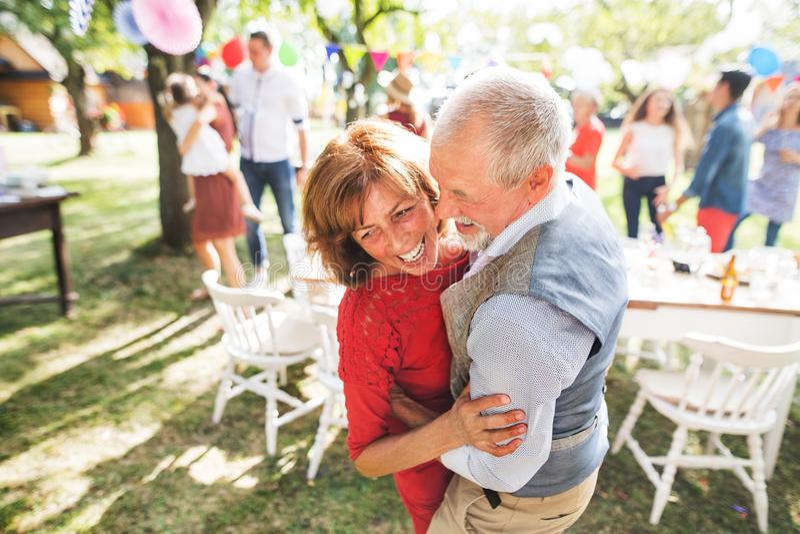 Un baile mayor de los pares en una fiesta de jardín afuera en el patio trasero imagen de archivo libre de regalías