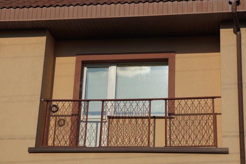 Un balcón abierto del metal con una puerta de cristal y una ventana en la pared marrón imágenes de archivo libres de regalías