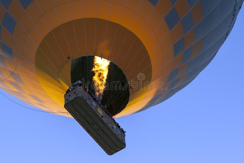Un ballon à air chaud se dirige vers le ciel au lever de soleil au-dessus de Goreme dans la région de Cappadocia de la Turquie image libre de droits