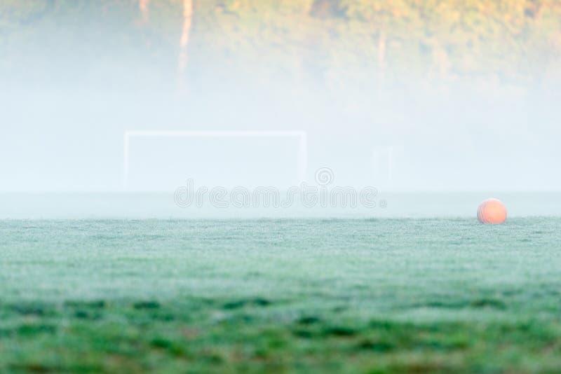 Un ballon de football orange décentré devant hors focale soc photo libre de droits