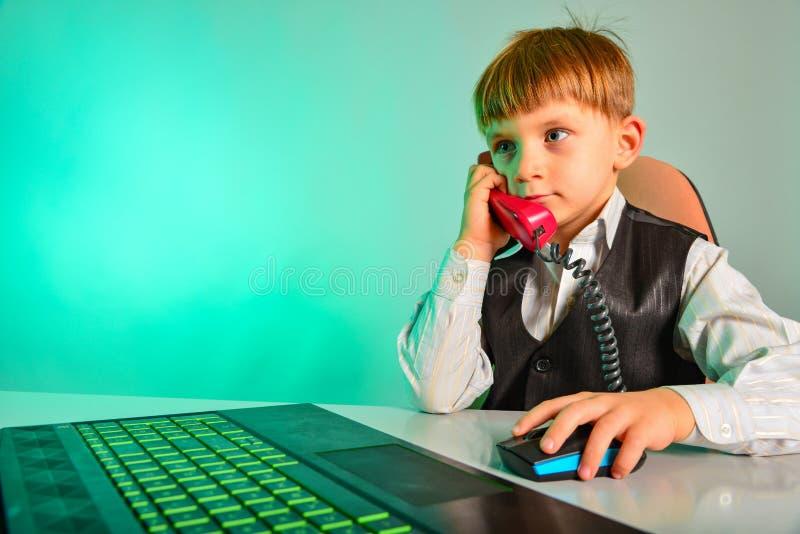 Un bambino ad un computer portatile nell'ufficio acconsente sugli argomenti da cavo, il concetto dell'affare dei bambini moderni immagini stock libere da diritti