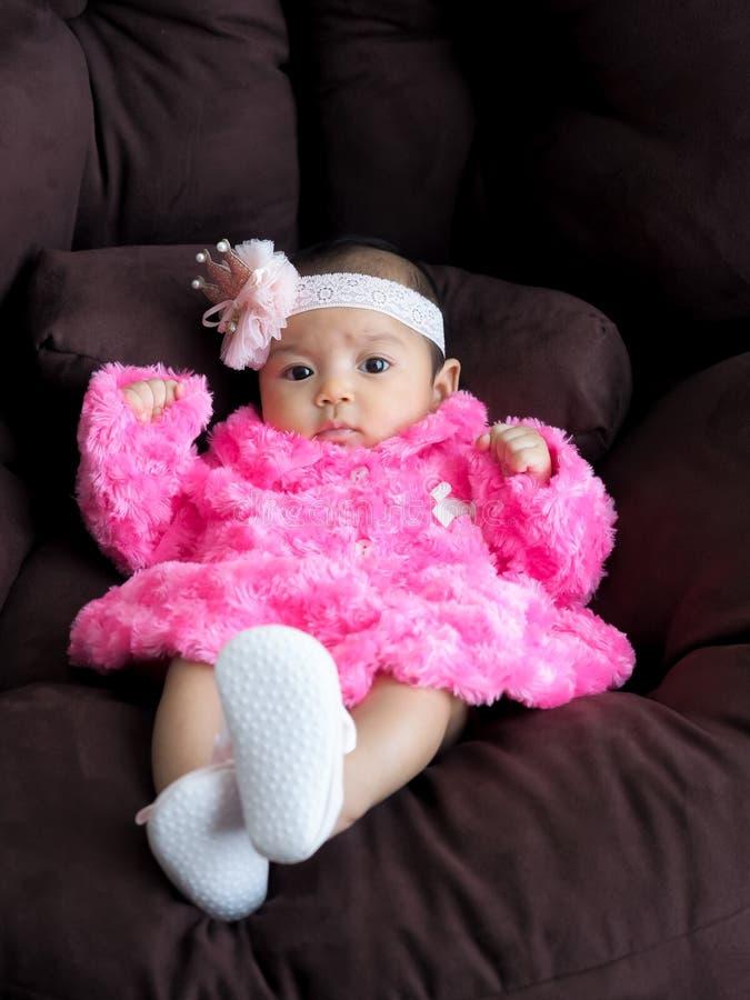 Un bambino asiatico della ragazza che porta una camicia rosa che si trova sul sofà con comodità fotografie stock libere da diritti