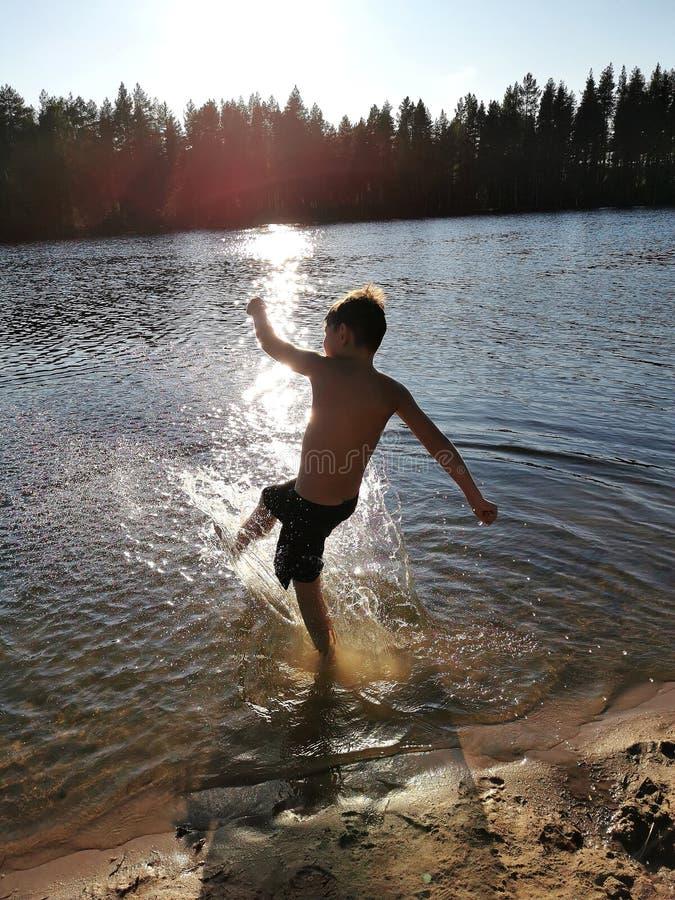 un bambino che gioca in acqua e fa schizzi, un bambino nuota nel lago o nel fiume e si diverte con le gocce fotografie stock libere da diritti