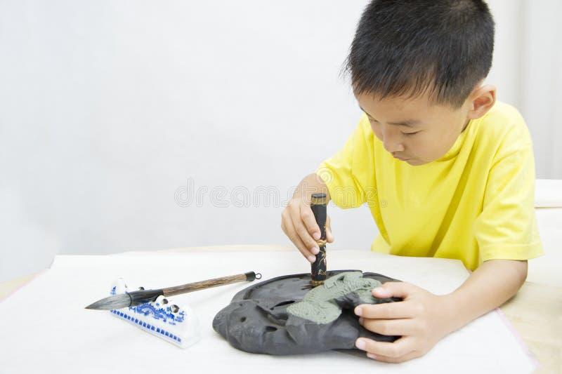 Un bambino che impara calligrafia cinese fotografia stock