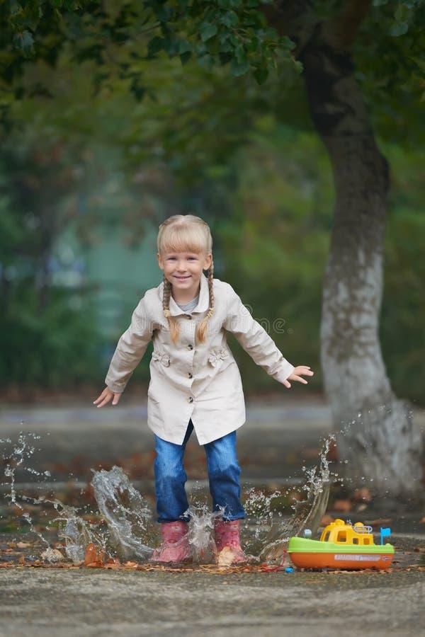 Un bambino che salta nella pozza subito dopo pioggia immagine stock