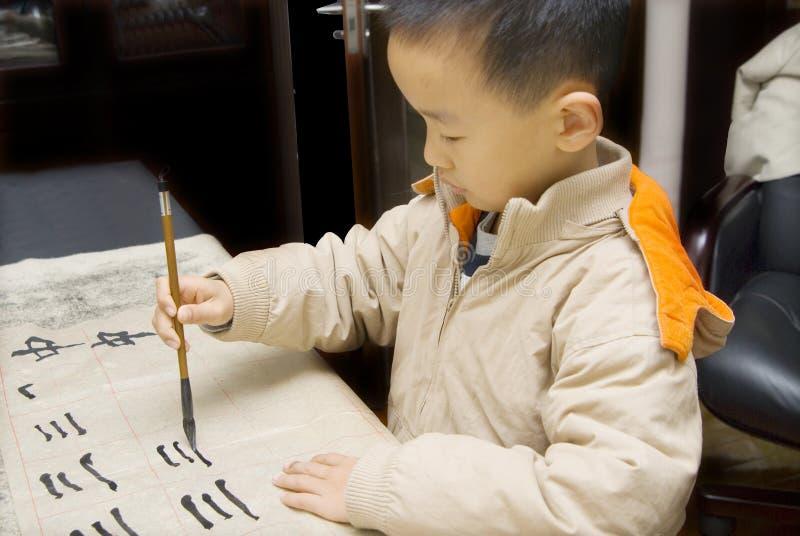 Un bambino che scrive calligrafia cinese fotografia stock