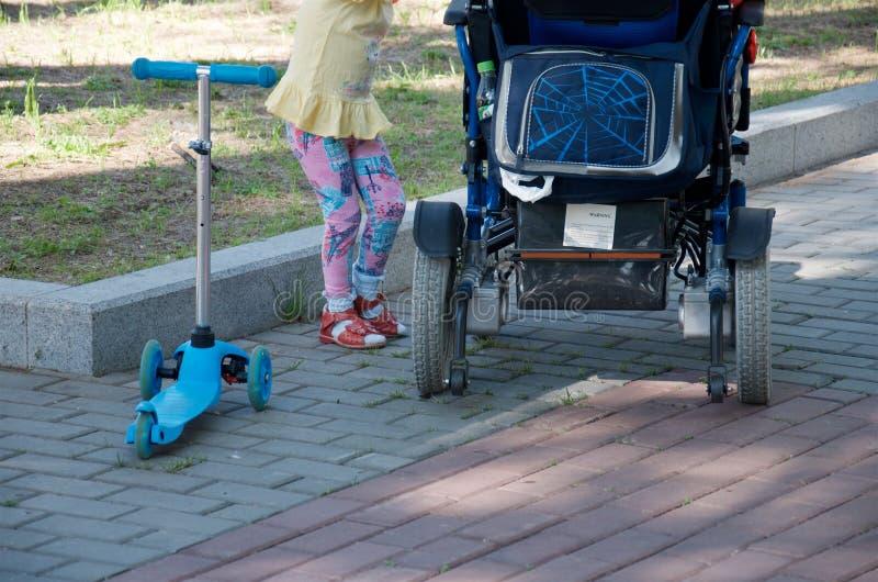 Un bambino con un motorino sta stando accanto alla sedia a rotelle del genitore immagine stock