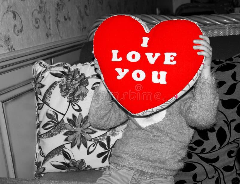un bambino copre il suo fronte di cuscino molle sotto forma di un cuore con ricamato ti amo fotografia stock